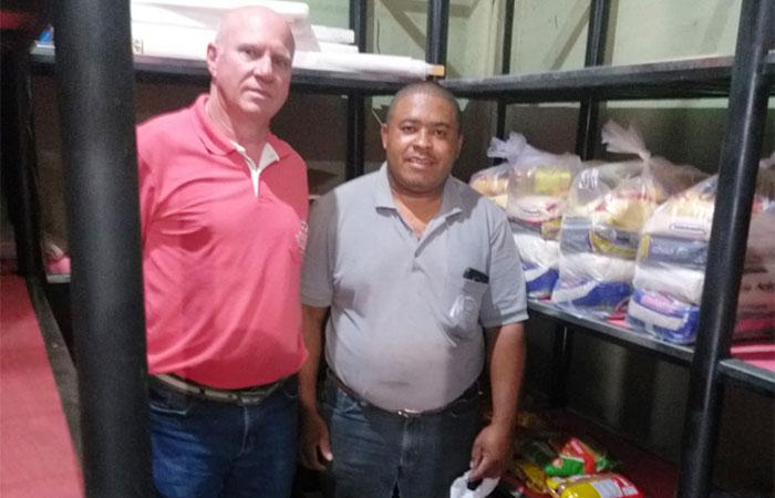 Funcionário da Paróquia Nossa Senhora de Lourdes, recebe do diretor do Sindicato de Londrina, Edvaldo Zanutto, as cestas básicas destinadas a famílias necessitadas